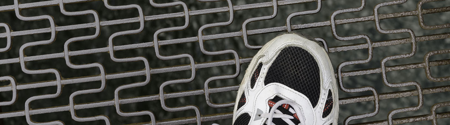 Sneaker over a metal grate-bridge