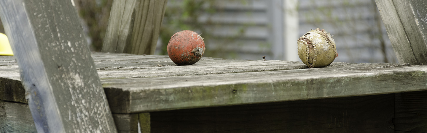 Old Baseballs, soaking some rays on an old wooden play set