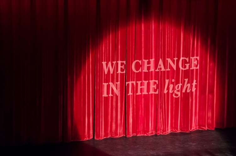 "Theatre Curtain - with the words ""we change in the light"" overlaid upon it."