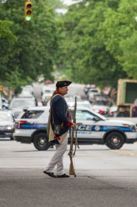 Patriot picket holds a musket, while a modern police cruiser blocks the road.