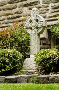 A stone cross adorning a memorial garden