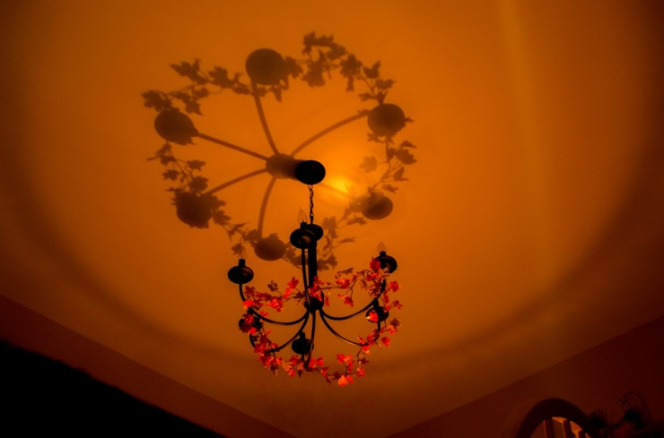 Shadow of a light fixture, cast on a ceiling.