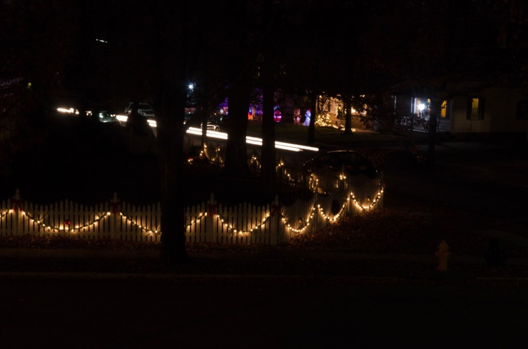 A light trail of headlights as a car drives through the frame. In the foreground Christmas lights glimmer.