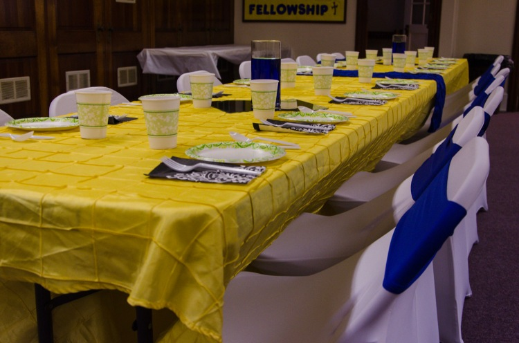 Covered chairs and lovely table linens make a drab social hall elegant