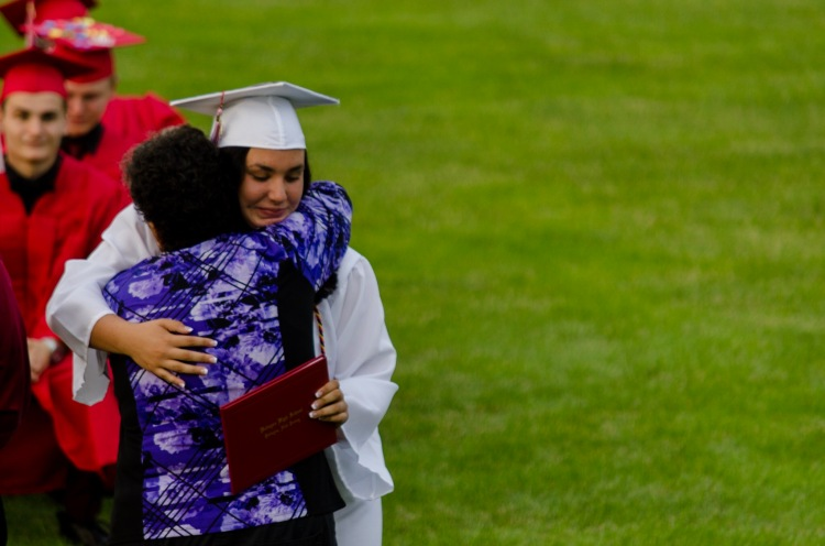 Councilwoman Gina Tait embraces her daughter after she accepts her diploma
