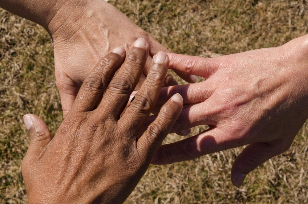 Hands overlay one another in gentleness and compassion