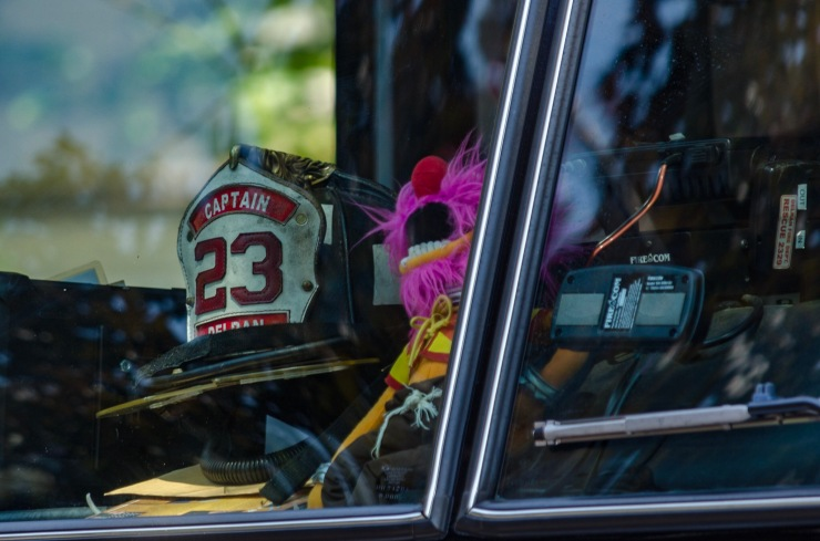 The Muppet, Animal, takes a ride on a firetruck