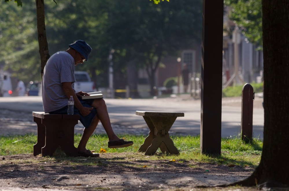 A man enjoys a book in the morning light on Duke of Gloucester Street
