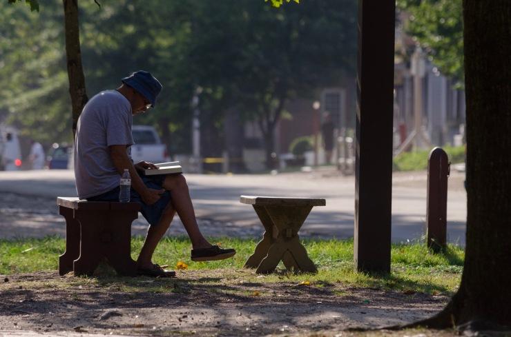 A man enjoys a book in the morning light on Duke of Gloucester Street