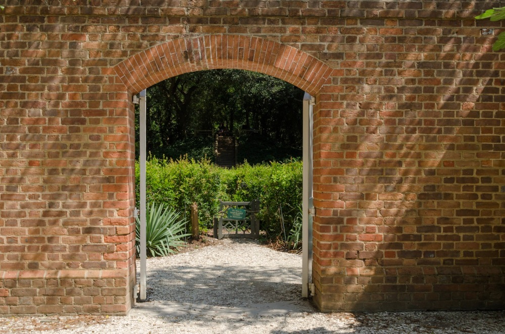 Open Gateway in a brick wall, A hedge maze is revealed on the other side.
