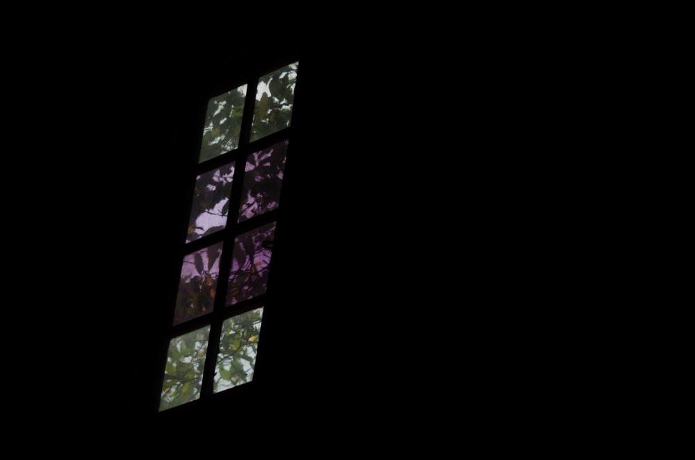 A window in the rafters, surrounded by darkness.