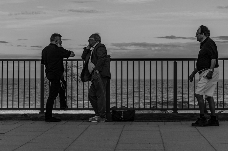Two friends talk by the ocean as people walk by on a promonade.