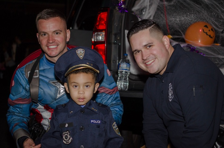Police pose with a child in costume.