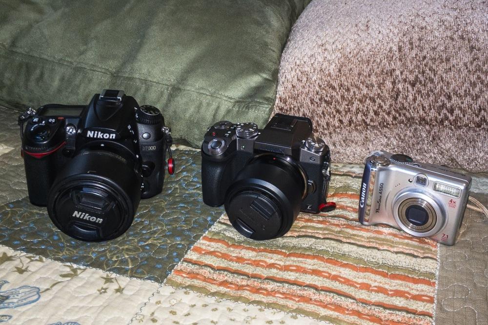Nikon D7000, Panasonic Lumix G7, and an older Canon Power Shot point and shoot.