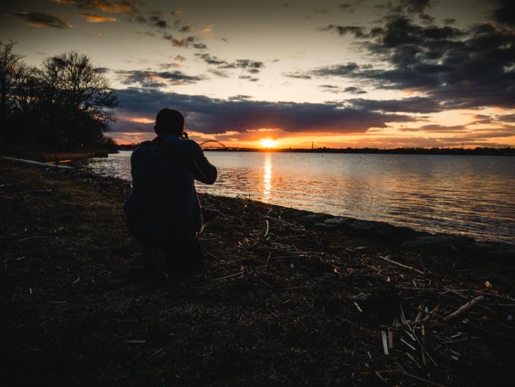 A photographer frames a shot of a sunset.