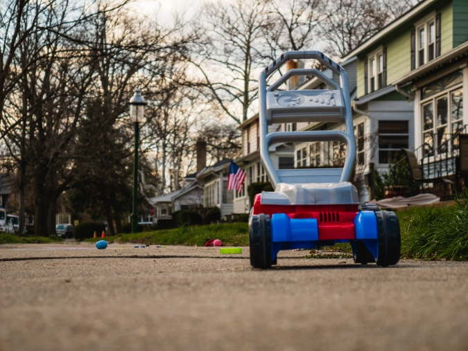 A toy mower out on the sidewalk