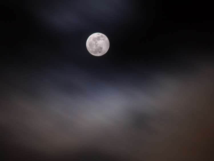 Near full moon surrounded by glowing clouds