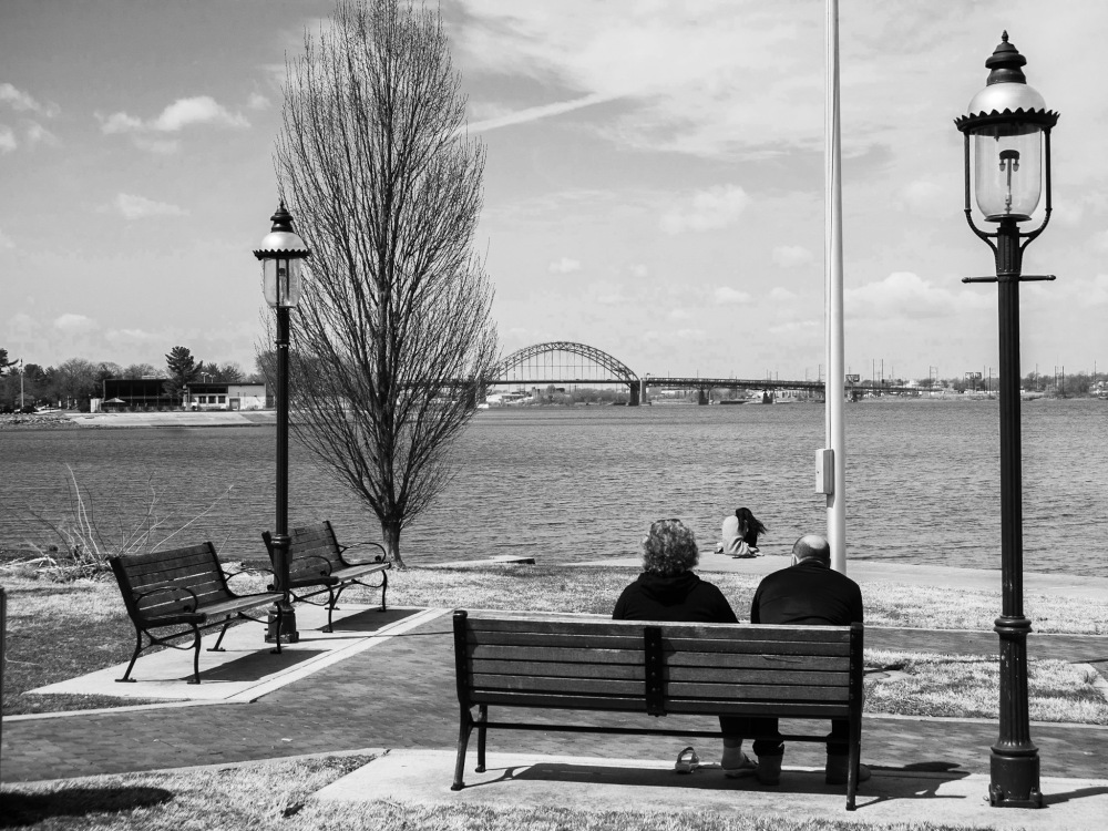 Three people form a triangle as they gaze upon the river.