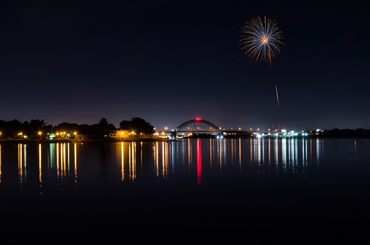 Nighttime photo of the Tacony-Palmyra Bridge. A masked firework photo is in the sky.