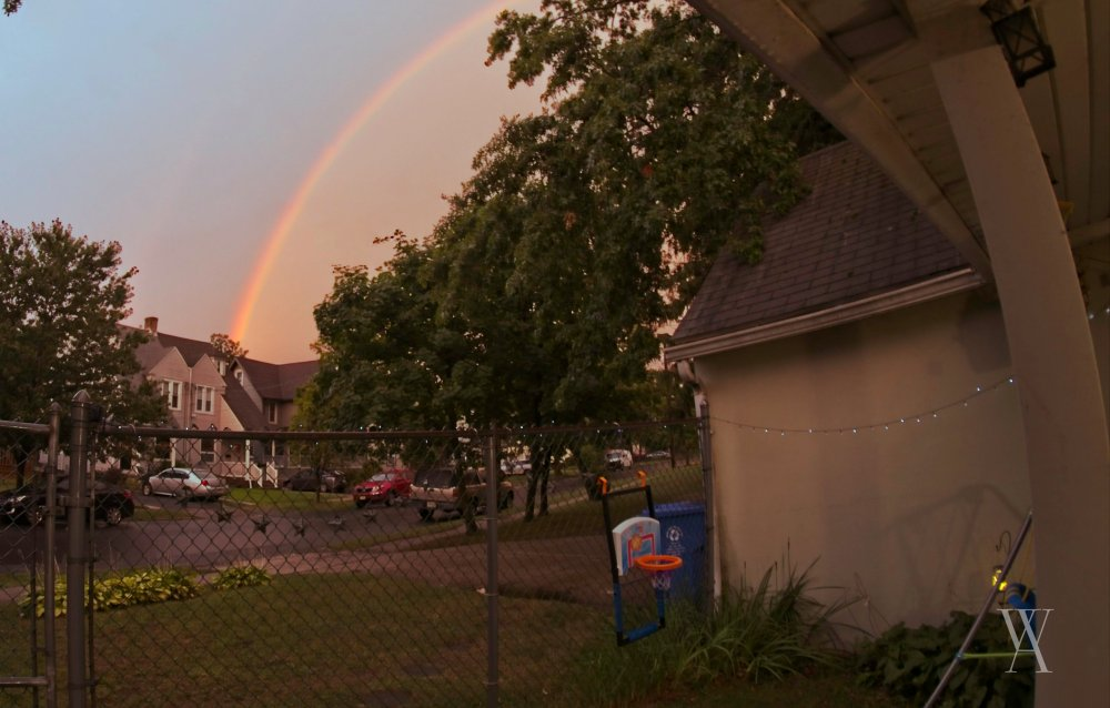 A rainbow appears in the midst of a thunderous evening.
